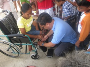 Fr. Tony Salas, SVD adjusts the wheelchair of a Tubigon Resident